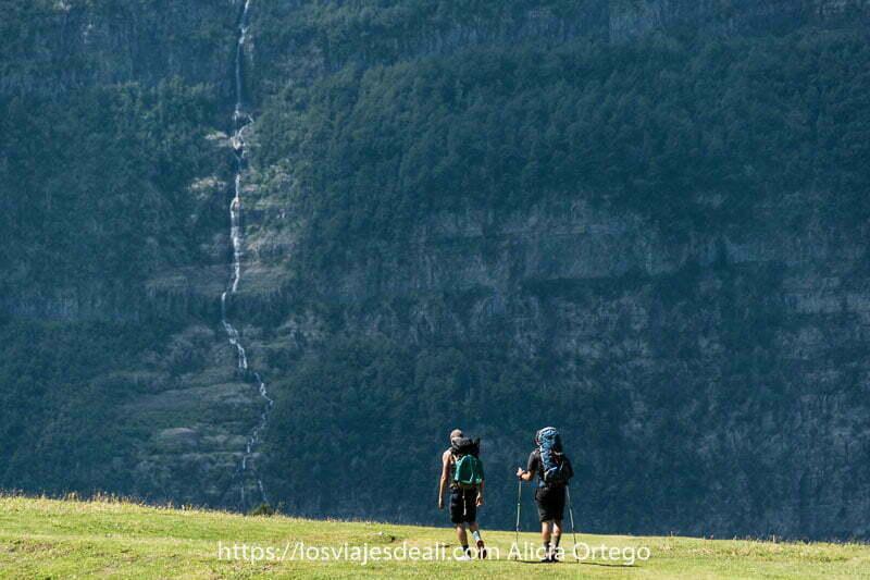dos chicos caminando con mochilas y al fondo una pared de roca y árboles con una cascada que baja en vertical en el Valle de Pineta