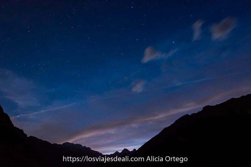 cielo estrellado con nubes rosas del atardecer en parte inferior y el perfil de las montañas del valle de pineta