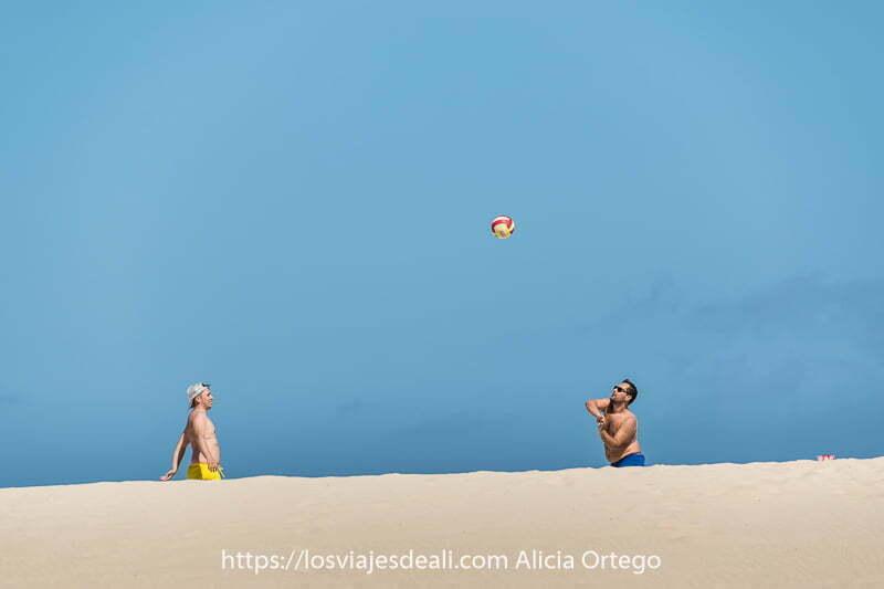 dos hombres jugando con una pelota que está en el aire contra cielo azul y duna blanca en parte inferior en fuerteventura