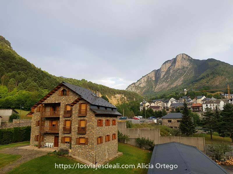 pueblo de Bielsa entre montañas y una casa de piedra con tejado de pizarra en primer plano