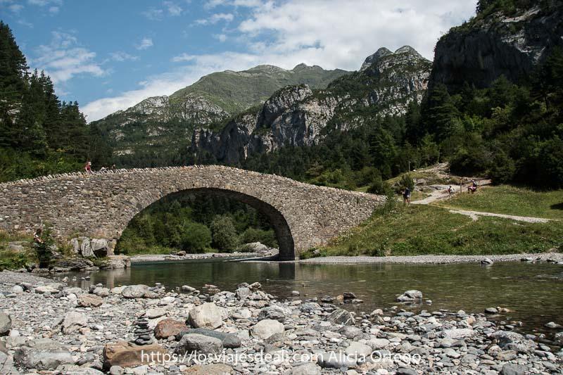 puente medieval románico con un solo arco cruzando el río con montañas detrás