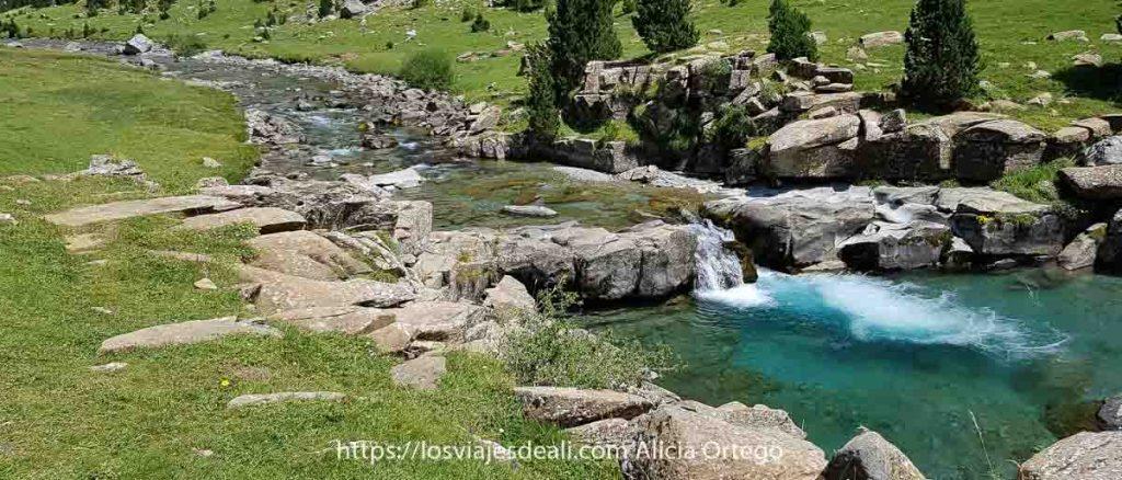 río entre prados con una poza de agua turquesa en el Pirineo aragonés