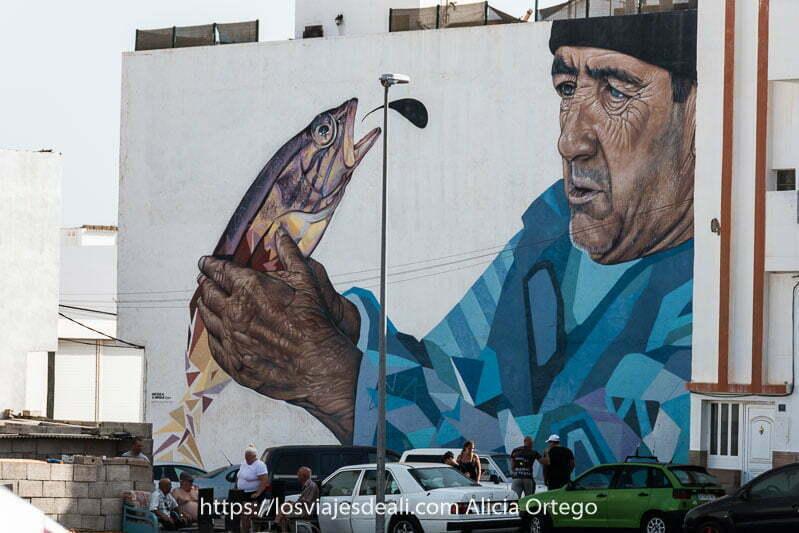 mural de Puerto del Rosario que muestra un pescador mirando un pez que tiene entre las manos