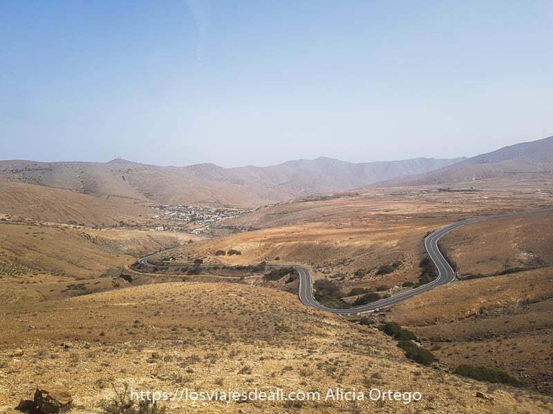 paisaje de montañas volcánicas con carretera con curvas y al fondo betancuria