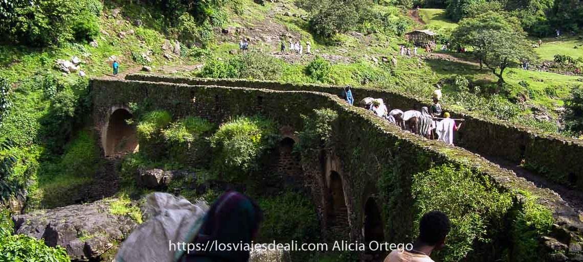 recuerdos de etiopía paisaje verde con puente de piedra medieval y etíopes cruzándolo