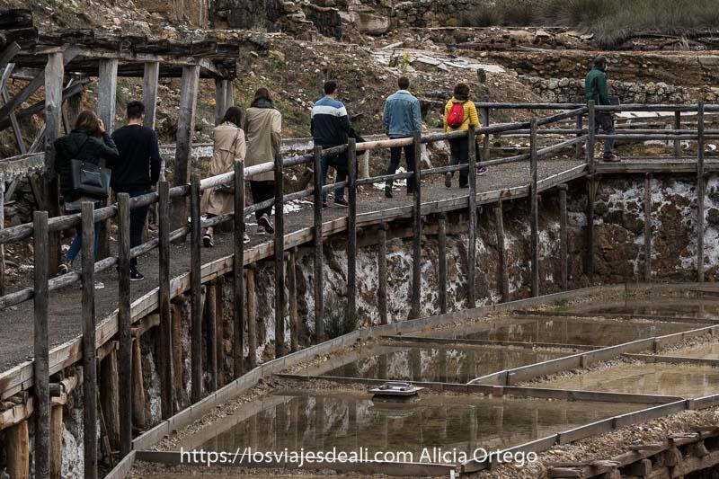 grupo de visitantes recorriendo las Salinas de Añana por un camino entre las piscinas