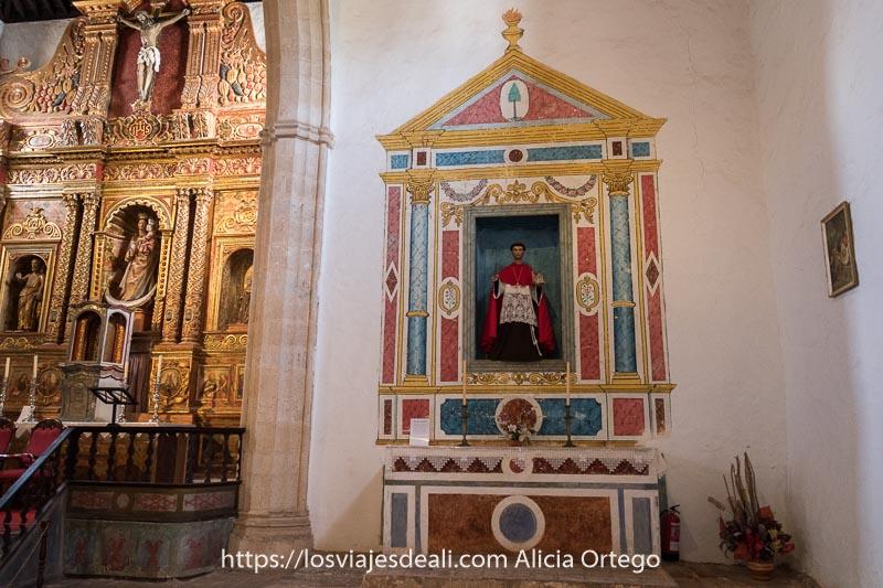 pequeño altar de la iglesia de betancuria con santo enmarcado en pintura que imita a edificio neoclásico de colores