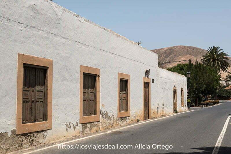 calle de betancuria con casa con ventanas y puerta de madera y marcos pintados de color beige