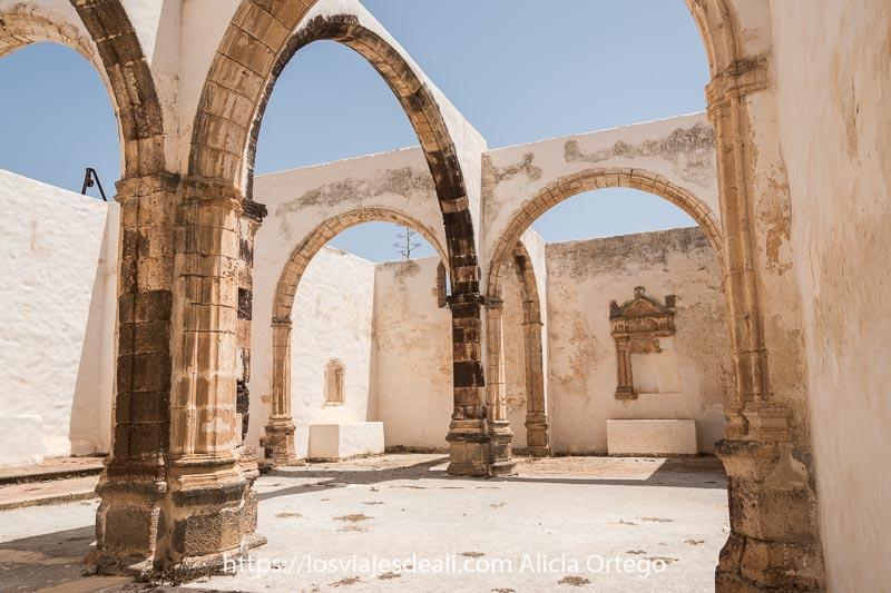 nave central de la iglesia conventual con arcos de piedra y al fondo hornacina barroca empotrada en la pared