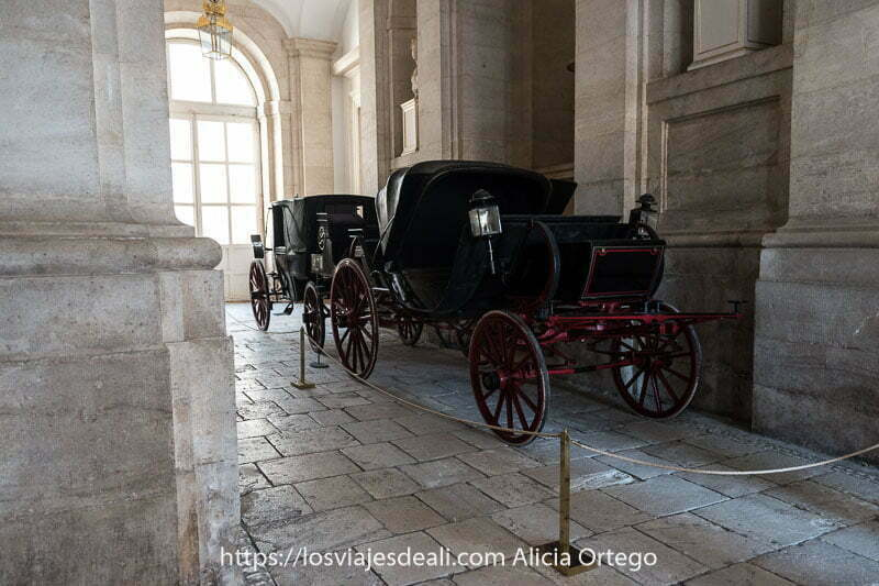 dos coches negros antiguos de madera con farolillos en la cochera del palacio real