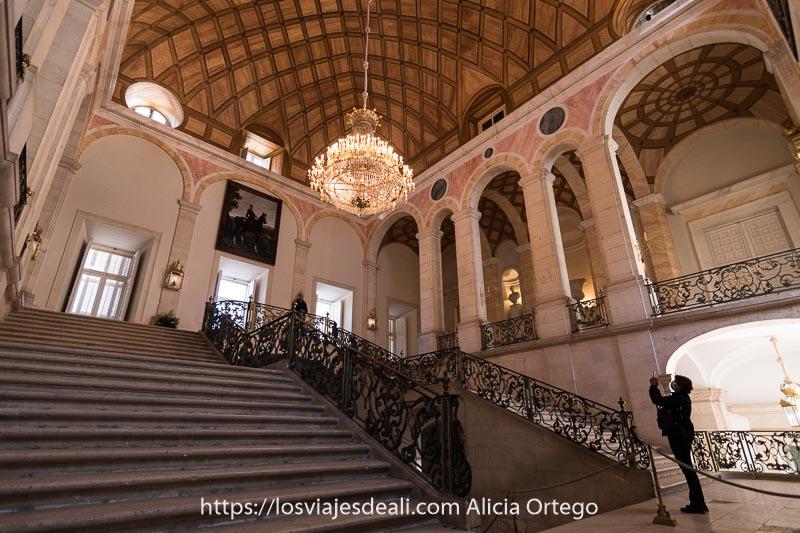 escaleras monumentales del palacio real de Aranjuez con una lámpara de araña enorme