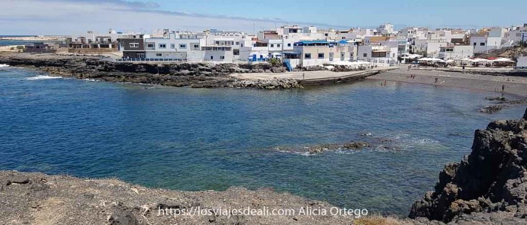 puerto de El Cotillo con playa de arena oscura y casas blancas con toques de azul