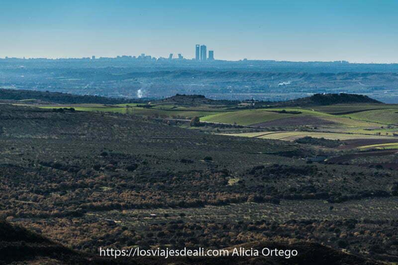 paisaje de campos verdes y al fondo silueta de las cuatro torres de madrid y las torres kio