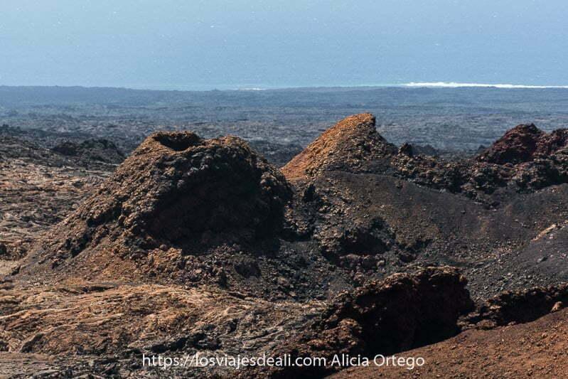 paisaje de timanfaya con cráter volcánico con colores amarillos y negros y al fondo el mar