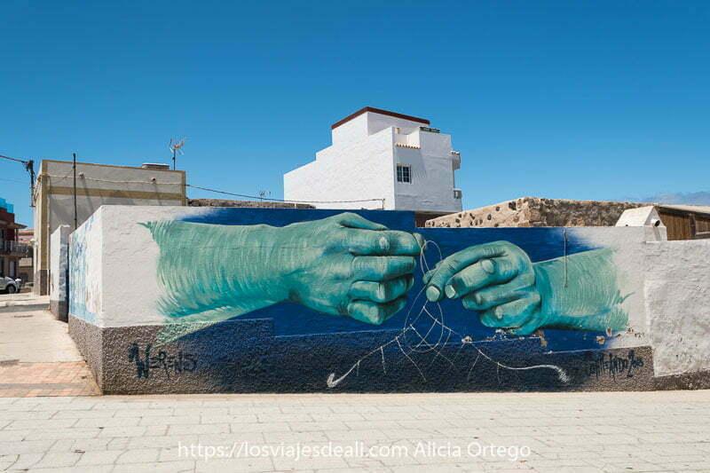 mural en una pared con dos manos de pescador cosiendo una red de pesca