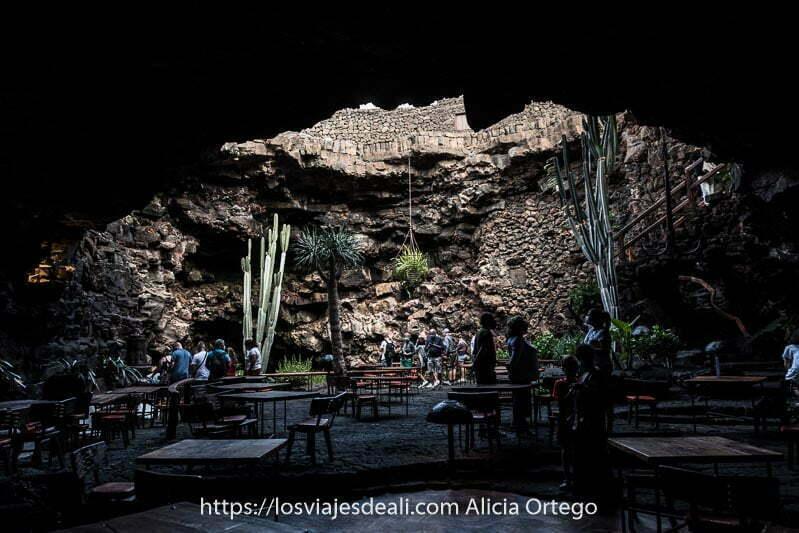 gente visitando los jameos entre mesas y sillas de una de las cafeterías y grandes cactus