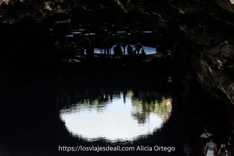 gente en sombras reflejándose en el agua de la laguna de los jameos