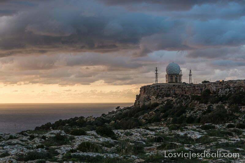 torre radar con cúpula blanca y nubes con colores de atardecer en los acantilados de dingli