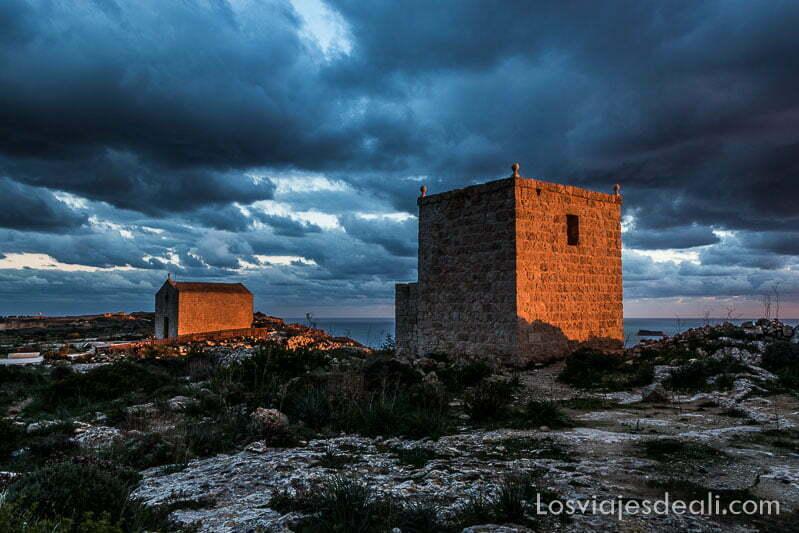 torre vigía de piedra y capilla un poco más adelante en suelo rocoso con mar detrás