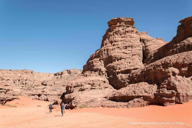personas andando junto a enormes columnas de roca con muchos agujeros y rugosidades en el sahara