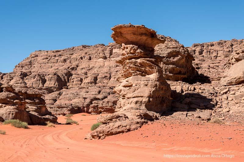 columna de roca que parece retorcida con muchos agujeros hechos por el viento y montaña detrás con suelo de arena roja