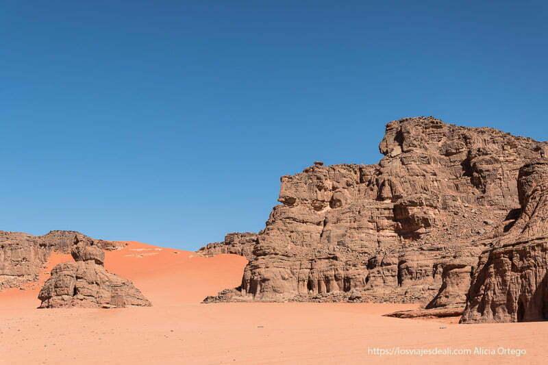 farallón de roca con columnas talladas por el viento y duna de arena roja con cielo muy azul en Le cirque de Ouanagan