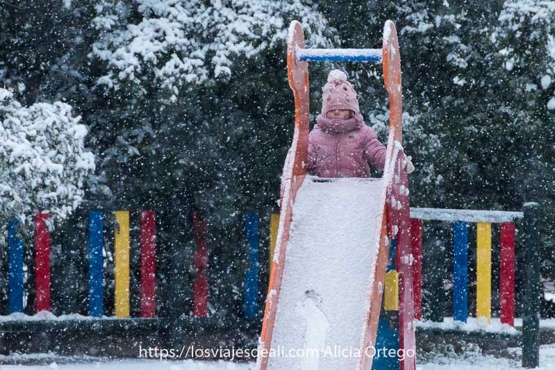 niña subiéndose a tobogán lleno de nieve mientras los copos siguen cayendo