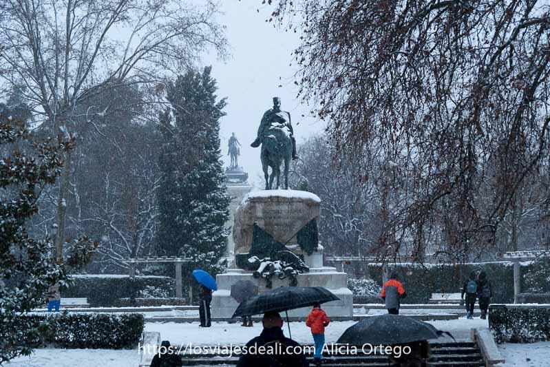 estatutas ecuestres en el retiro mientras nieva y la gente va con paraguas