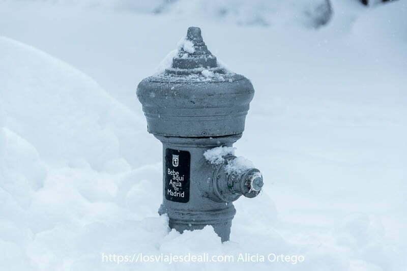 """fuente de agua con cartel que dice """"bebe aquí agua de madrid"""" medio enterrada en nieve"""