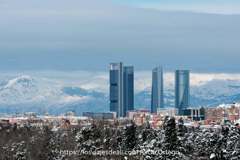 las cuatro torres de madrid con la sierra detrás nevada