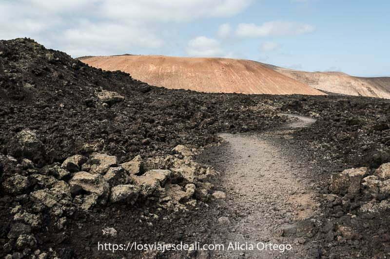 camino entre campos de lava negra con caldera blanca al fondo de color anaranjado