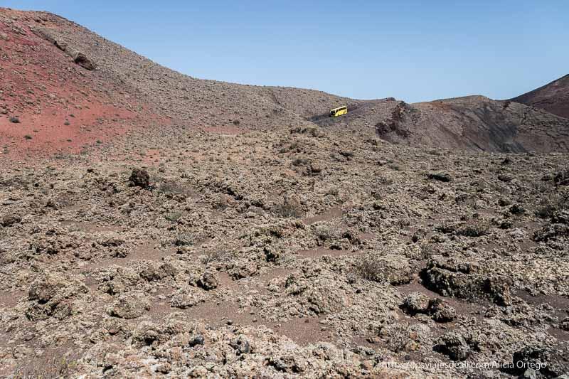 autobús amarillo bajando cuesta entre laderas de lava de distintos colores y líquenes