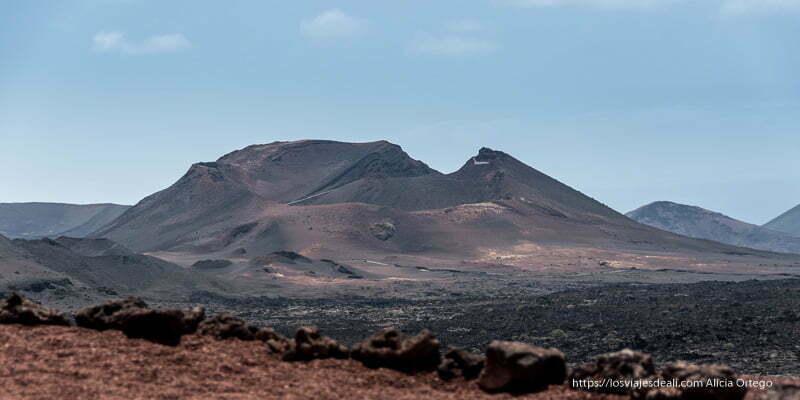 gran volcán de perfil recortado en cielo azul con laderas rojizas y blanquecinas
