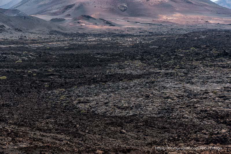 mar de lava negra y gris con falda de volcán rojizo al fondo