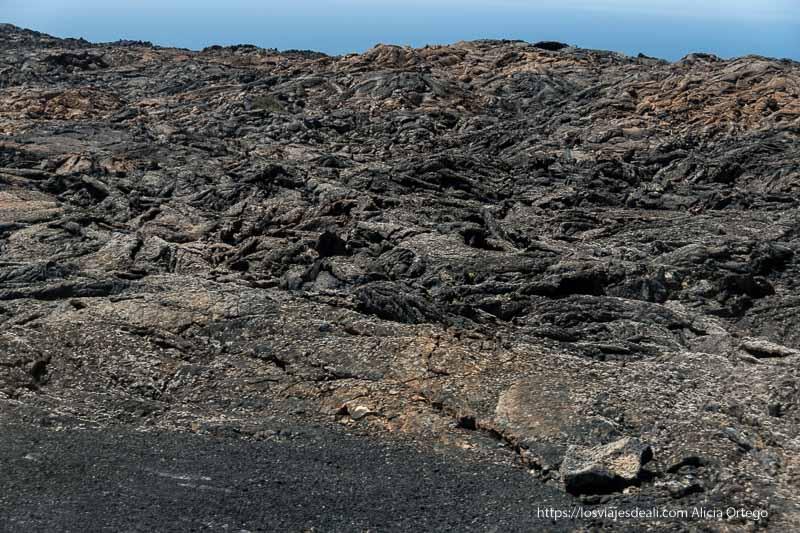 mar de lavas retorcidas con mar azul al fondo en el parque nacional de timanfaya