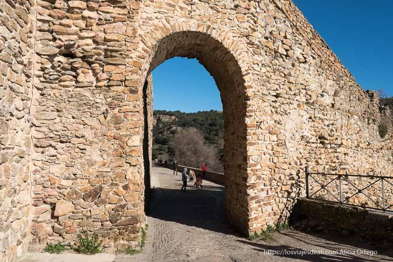 arco de piedra adosado a la muralla para continuar por paseo empedrado junto al río