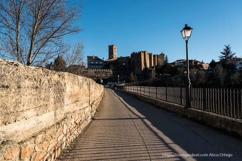 cruzando el puente viejo con las murallas y la torre de la iglesia al fondo
