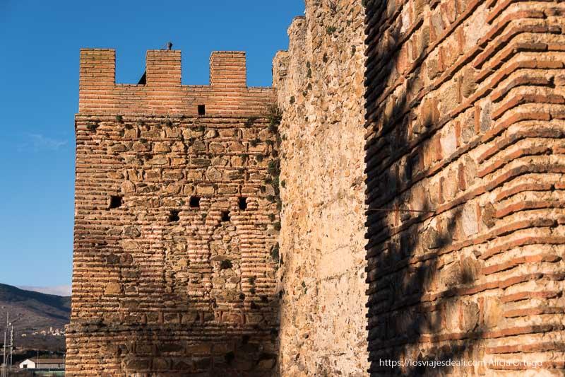 murallas de cerca con torre sobresaliendo, hechas de piedra y ladrillo rojo