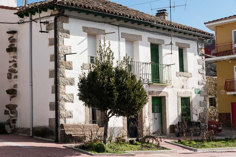 casa de canencia con fachada blanca y piedras de granito en las esquinas y los dinteles de ventanas y puertas