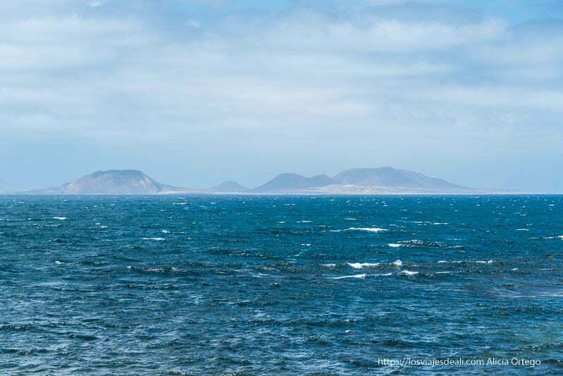 isla de la graciosa en el horizonte con el mar en primer plano
