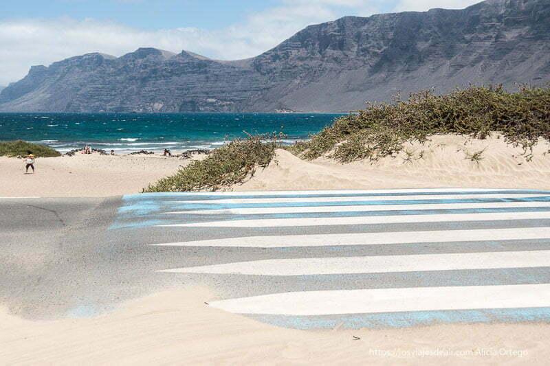 paso de cebra con arena y dunas en un lado y detrás los riscos de famara y el mar