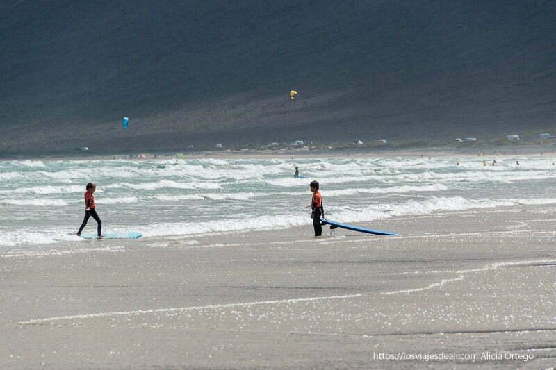 un niño llega a la orilla montado en su tabla de surf y otro le espera con la suya