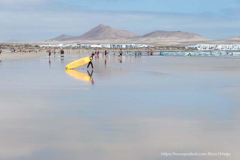 chico llevando su tabla de surf amarilla hacia el agua reflejándose en la arena mojada