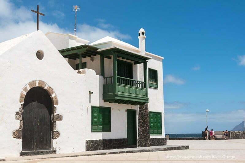 pequeña iglesia con paredes encaladas y piedras volcánicas y casa junto a ella con balcón de madera pintado de verde