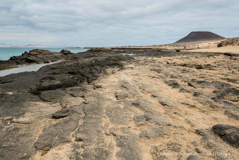 plataforma de roca volcánica semicubierta de arena que termina en mar de aguas turquesas y volcán al fondo