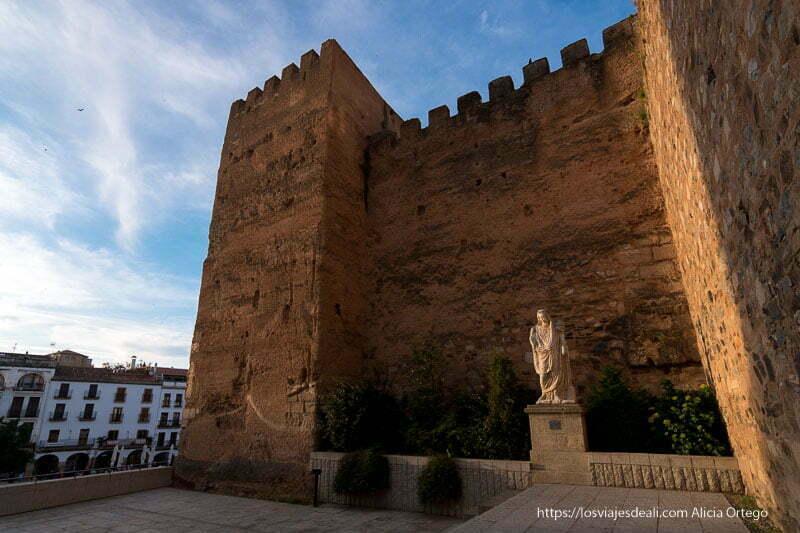 muralla y torre al atardecer y estatua de diosa griega junto a la plaza mayor