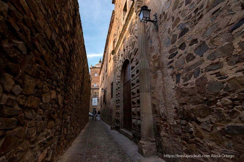 calle estrecha entre muralla y palacio con puerta decorada en piedra