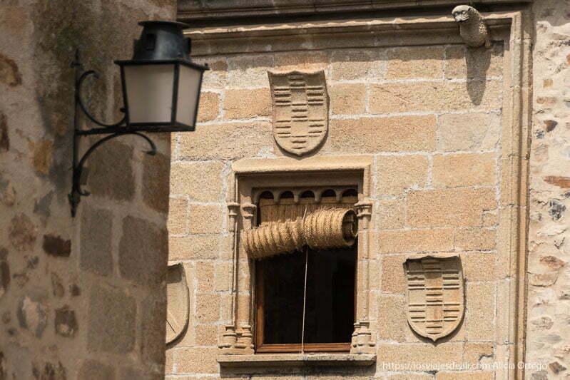 ventana de palacio con tres escudos alrededor y persiana hecha de fibra