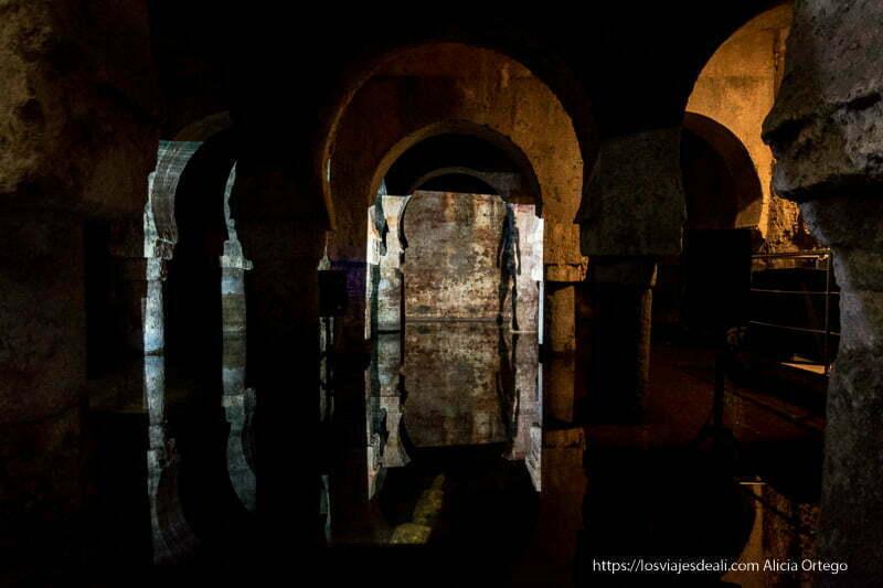 aljibe árabe del museo de cáceres con arcos en piedra que se reflejan en el agua