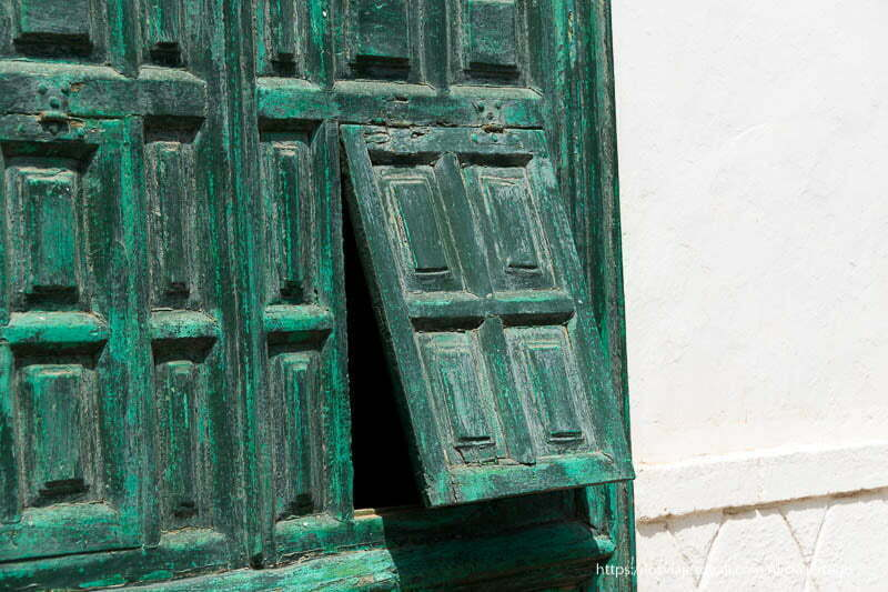 apertura de un cuarterón de una puerta de madera pintada de verde en teguise